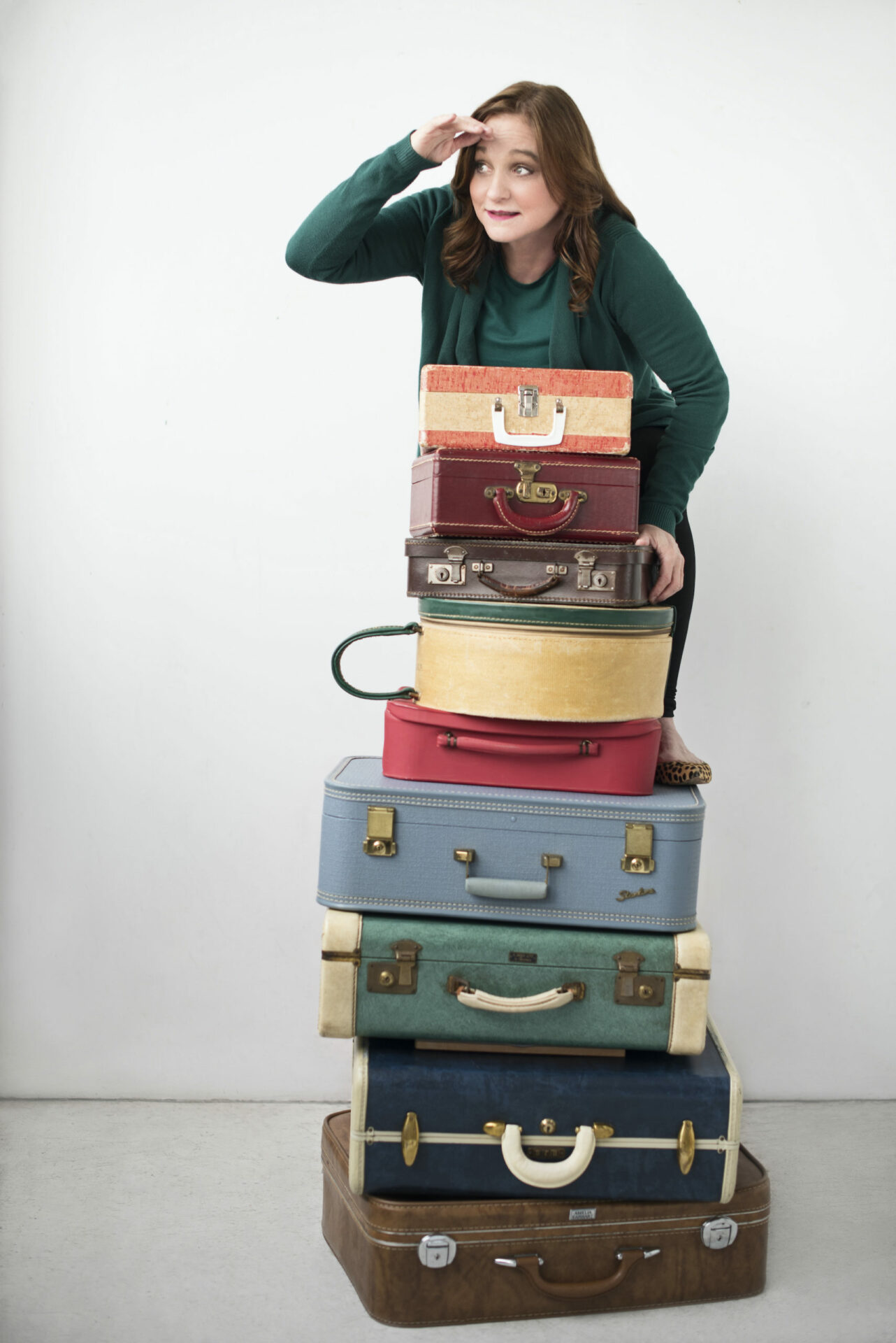 Stack of suitcases with Lori Hamiton peering over it